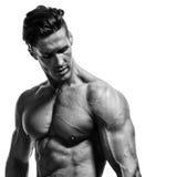 De jonge knappe bodybuilder toont spieren op de wapens, borst en Stock Foto