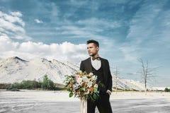 De jonge knappe elegante mens in modieuze kostuum en vlinderdas houdt een groot boeket van bloemen en bekijkt aan kant stock afbeeldingen