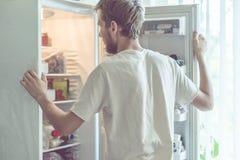De jonge knappe gebaarde mens die dichtbij opended thuis koelkastkeuken bevinden zich royalty-vrije stock foto's