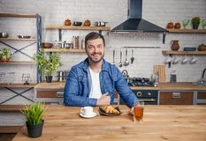 De jonge knappe het glimlachen kerel zit bij de keuken klaar om zijn ontbijtcroissant, koffie en een appelsap te hebben stock foto's