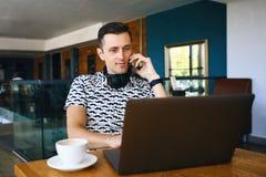 De jonge knappe hipstermens gebruikt laptop, die mobiele telefoon in cafetaria spreken royalty-vrije stock afbeeldingen