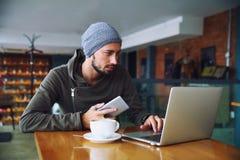 De jonge knappe hipstermens met baard gebruikt computer in cafetaria royalty-vrije stock foto