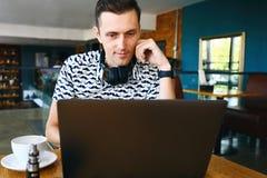 De jonge knappe hipstermens in zonnebril gebruikt laptop in cafetaria royalty-vrije stock fotografie