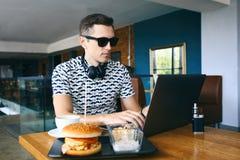 De jonge knappe hipstermens in zonnebril gebruikt laptop in cafetaria Kop van koffie, elektronische sigaret en royalty-vrije stock afbeeldingen