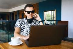 De jonge knappe hipstermens in zonnebril gebruikt laptop, die mobiele telefoon in cafetaria spreken stock foto's