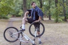 De jonge knappe Kaukasische mens bevindt zich been op de fiets in a exhaggerated trots stijl Witte oortelefoons, toevallige buite royalty-vrije stock foto