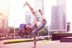 De jonge knappe kerel bevindt zich op de hand op de achtergrond van het stedelijke landschap Modieuze danser op stadsachtergrond Stock Foto's