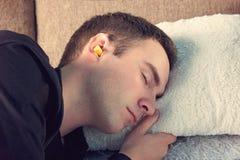 De jonge knappe kerel is in slaap dragend zwarte t-shirt Sluit omhoog portret Dagrust, Siësta gele oorstoppen in de oren van mens royalty-vrije stock foto's