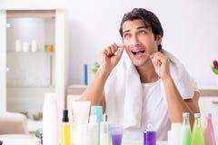 De jonge knappe man in de badkamers in hygiëneconcept royalty-vrije stock afbeeldingen