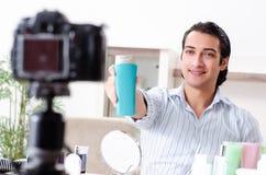 De jonge knappe man die zijn blog in hygiëneconcept registreren stock fotografie