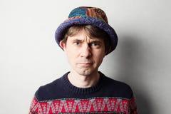 De jonge knappe mens breit binnen kleurrijke kleren Stock Afbeelding