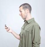 De jonge knappe mens die verraste de telefoon kijken stock foto