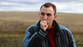 De jonge knappe mens hoest of niest openlucht stock footage