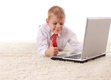 De jonge knappe mens ligt op een witte achtergrond met witte laptop Royalty-vrije Stock Foto's