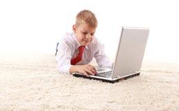De jonge knappe mens ligt op een witte achtergrond met witte laptop Royalty-vrije Stock Foto