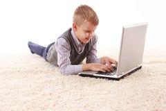 De jonge knappe mens ligt op een witte achtergrond met witte laptop Royalty-vrije Stock Afbeeldingen