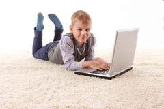 De jonge knappe mens ligt op een witte achtergrond met witte laptop Stock Foto's