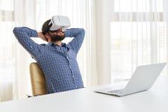 De jonge knappe mens ontspant in 3d virtuele glazen Stock Foto