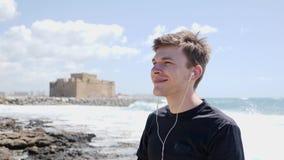 De jonge knappe mens zet de oortelefoons v??r looppastraining die zich op strand het glimlachen bevinden aan Kasteel op de achter stock video