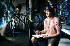 De jonge knappe modieuze mens in een GLB en met een tatoegerings kleine bedrijfseigenaar die een fiets verkopen, de workshop zit  stock foto's