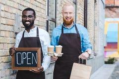 de jonge knappe multi-etnische eigenaars van koffiewinkel in schorten met teken open document zakken en beschikbare koffie vormt  stock afbeelding