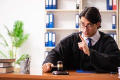 De jonge knappe rechter die voor het gerecht werken stock fotografie