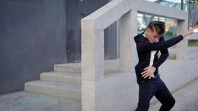 De jonge knappe straatdanser leidt zijn bewegingen in een stad op, danst en geniet van in een stad stock videobeelden
