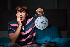 De jonge knappe student die voor examens bij nacht voorbereidingen treffen royalty-vrije stock fotografie