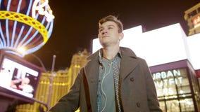 De jonge knappe toerist loopt op een verlichte straat in Vegas stock video