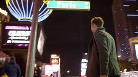 De jonge knappe toerist spreekt over zijn smartphone terwijl het lopen onderaan de verlichte straat in Las Vegas stock video