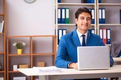 De jonge knappe zakenman die in het bureau werken royalty-vrije stock foto's