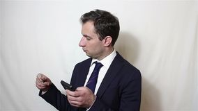 De jonge knappe zakenman gaat gegevens van zijn creditcard in smartphone in stock video