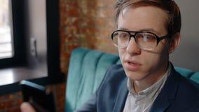 De jonge knappe zakenman gebruikt smartphone, zittend bij lijst in koffie, kerel die in glazen het telefoonscherm bekijken stock video