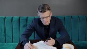 De jonge knappe zakenman gebruikt telefoon, zittend bij bureau met notitieboekje in koffie stock videobeelden