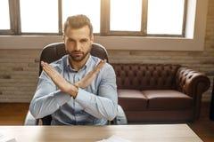De jonge knappe zakenman zit bij lijst in zijn eigen bureau Hij houdt handen in verboden teken worden gekruist dat Boos en zeer stock fotografie