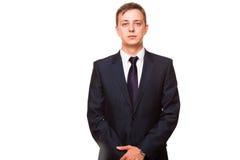 De jonge knappe zakenman in zwart kostuum bevindt zich rechtstreeks die, portret op witte achtergrond wordt geïsoleerd stock afbeelding