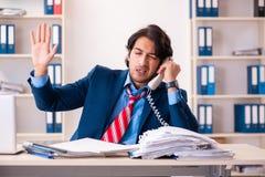 De jonge knappe zakenmanzitting in het bureau royalty-vrije stock fotografie