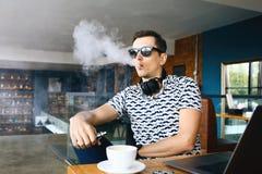 De jonge knappe zitting van de hipstermens insunglasse in koffie met een kop koffie, het vaping en versies een wolk van damp stock afbeelding
