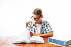 De jonge knappe zitting van het de lezingsboek van de tienerkerel bij lijst, schooljongen of student die thuiswerk, in Studio doe stock afbeeldingen