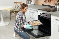 De jonge koekjes van het vrouwenbaksel in oven royalty-vrije stock afbeelding