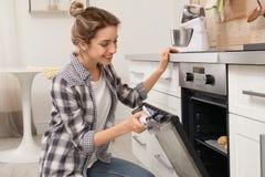 De jonge koekjes van het vrouwenbaksel in oven stock afbeelding