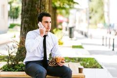De jonge Koffie van Zakenmaneating and drinking terwijl het Spreken op Telefoon royalty-vrije stock foto