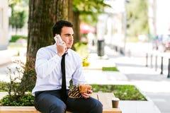 De jonge Koffie van Zakenmaneating and drinking terwijl het Spreken op Telefoon royalty-vrije stock afbeeldingen