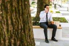 De jonge Koffie van Zakenmaneating and drinking terwijl het Spreken op Telefoon stock afbeeldingen