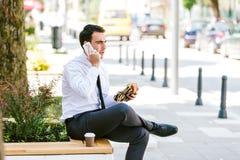 De jonge Koffie van Zakenmaneating and drinking terwijl het Spreken op Telefoon stock afbeelding