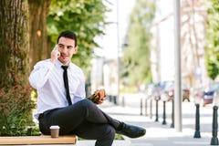 De jonge Koffie van Zakenmaneating and drinking terwijl het Spreken op Telefoon royalty-vrije stock afbeelding