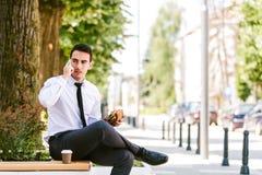 De jonge Koffie van Zakenmaneating and drinking terwijl het Spreken op Telefoon stock foto