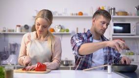 De jonge kokende groenten van het veganistpaar, gezonde voeding, gelukkige tijd samen stock video