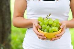 De jonge kom van de vrouwenholding met druiven Stock Afbeelding