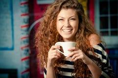 De jonge kop van de vrouwenholding van koffie buiten koffie royalty-vrije stock afbeelding